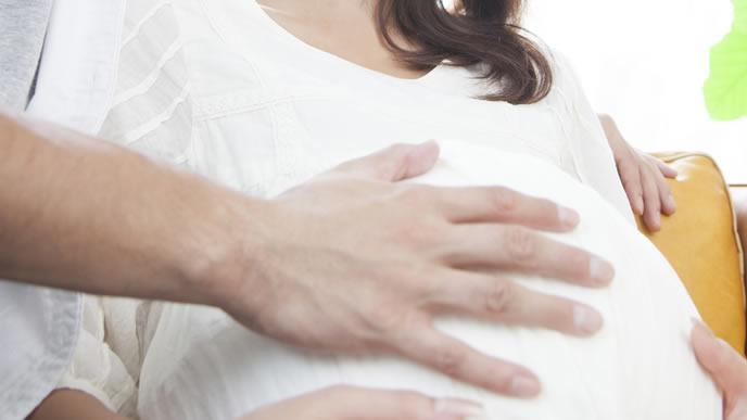 妻の胎動を手で確かめる夫