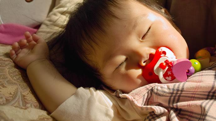 可愛いバンザイ寝で眠る生後3ヶ月の赤ちゃん
