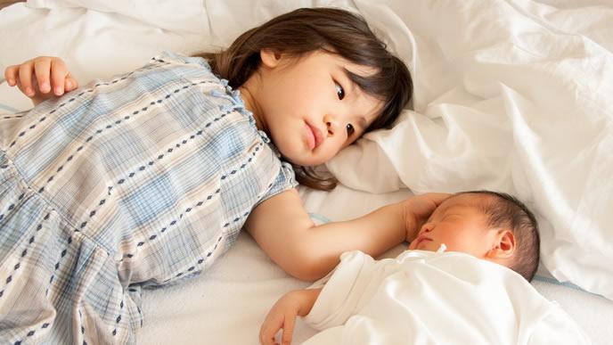寝ている妹を愛おしそうに撫でる女の子