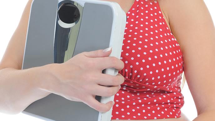 体重計を手に抱える食べ過ぎの妊婦