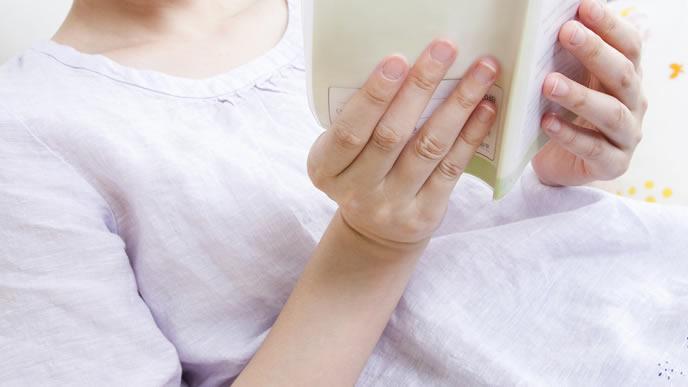 母子手帳を広げ臨月の状態を確かめる妊婦