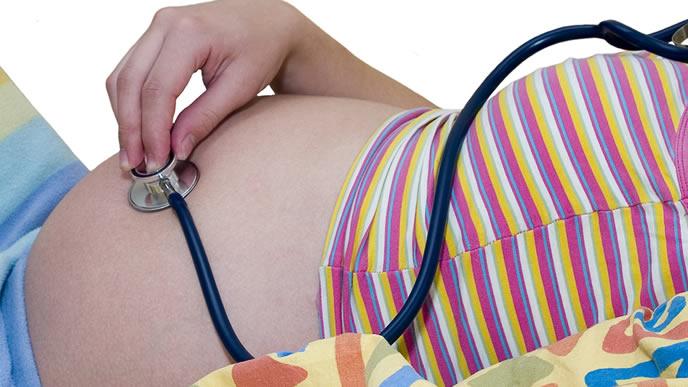 赤ちゃんの様子を聴診器で確かめる妊婦