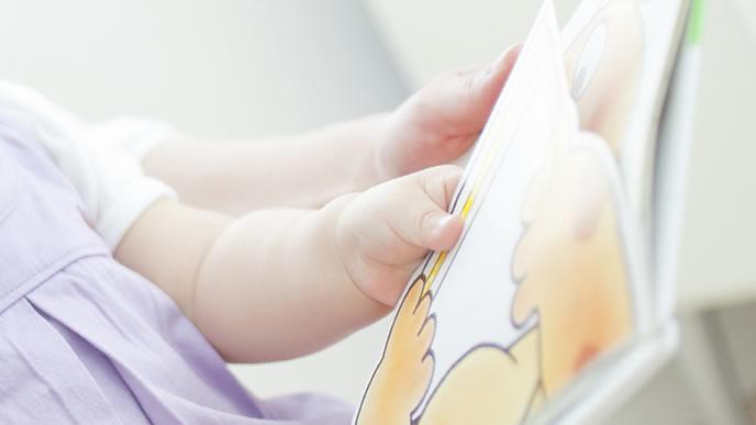 ママに絵本を読んでもらう女の子の赤ちゃん