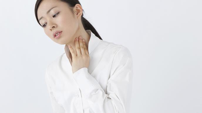 首に手を当て熱を測る女性