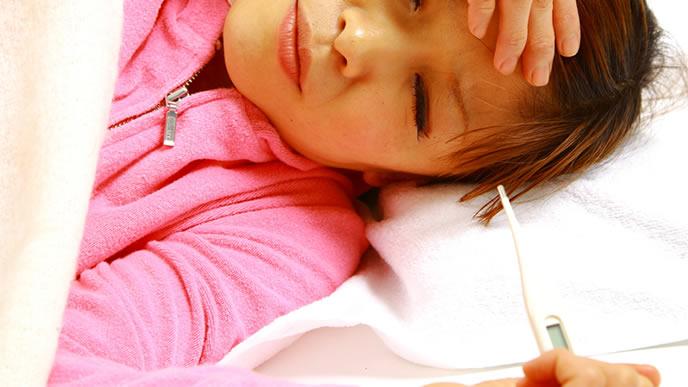 体温計で熱を図っているが実は妊娠している女性