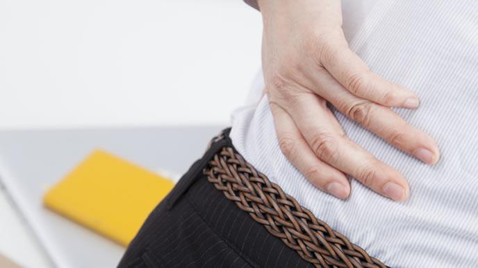 産後の腰痛に悩まされ腰に手を当てるママ
