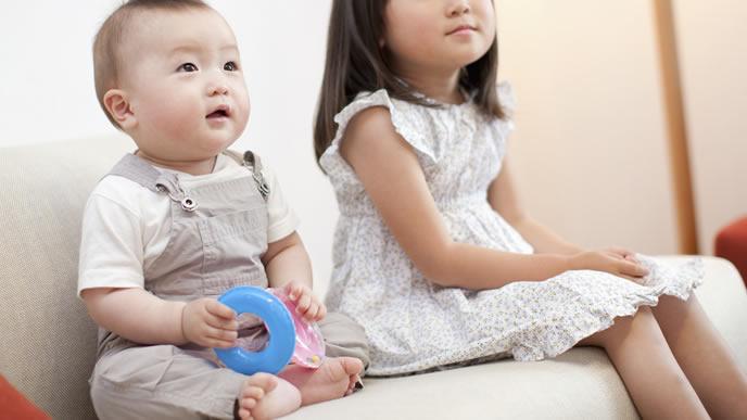 兄弟とテレビを見ながらおもちゃで遊ぶ赤ちゃん