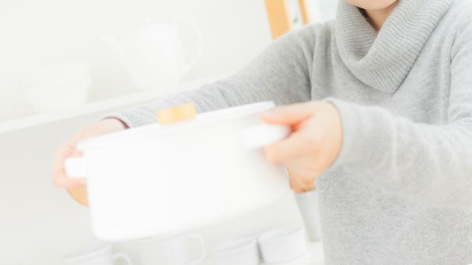 鍋で離乳食のおかゆを作るママ