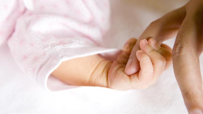 ママの指を必死につかむ新生児の赤ちゃん