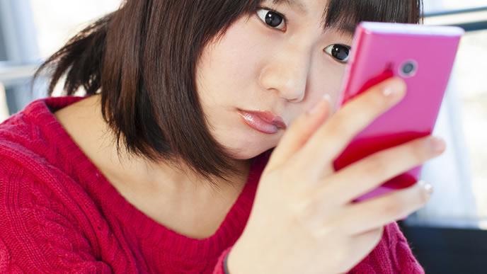 スマートフォンのゲームでストレス発散をする女性