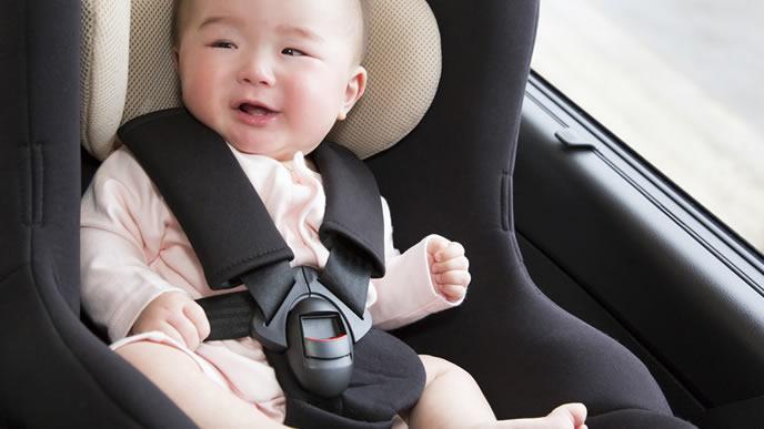 旅行に出かけるためにベビーシートに載せられる赤ちゃん