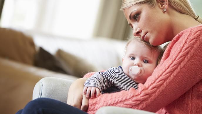 離乳食を食べてくれない赤ちゃんを心配そうに抱くママ