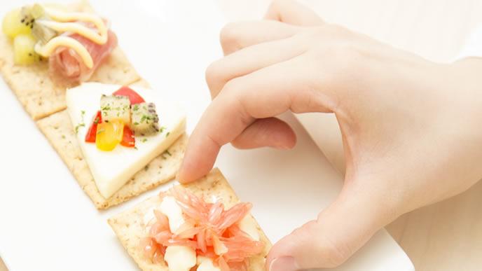クラッカー乗ったチーズを食べる妊娠超初期の女性