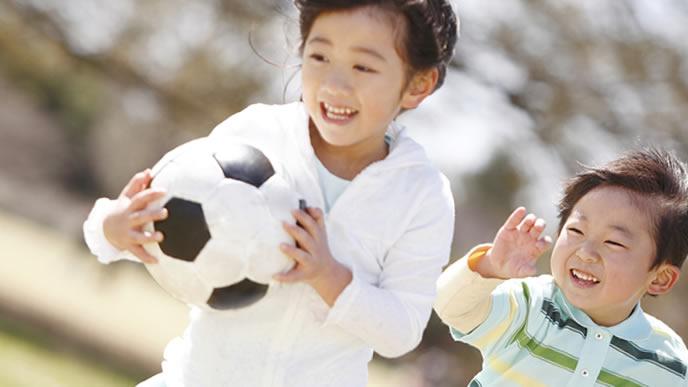 サッカーボールを抱えて楽しく遊ぶ姉弟