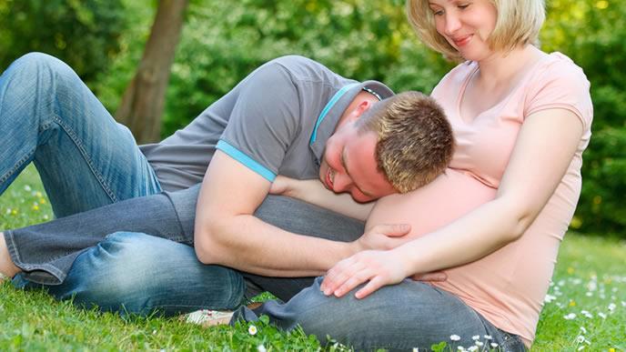 必死に赤ちゃんのお腹の胎動を聞こうとするパパ