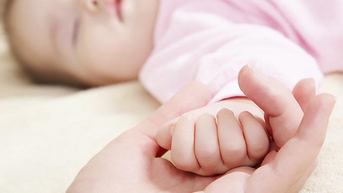 クループ症候群の赤ちゃんの手を握るママ