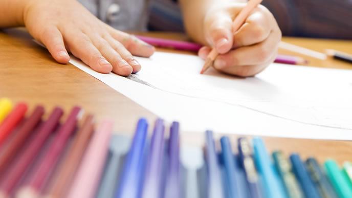 色鉛筆で絵を書く幼児