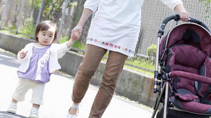 ベビーカーから降りてママと手を繋ぐ赤ちゃん
