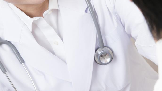 体調が思わしくない女性の診察をする医師