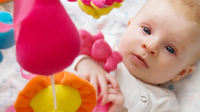 頭上で回るメリーを見つめる赤ちゃん