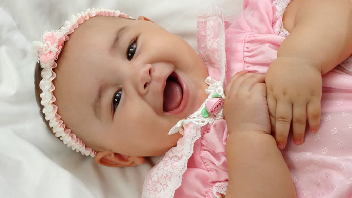 お宮参りに行くベビードレスを試着する赤ちゃん