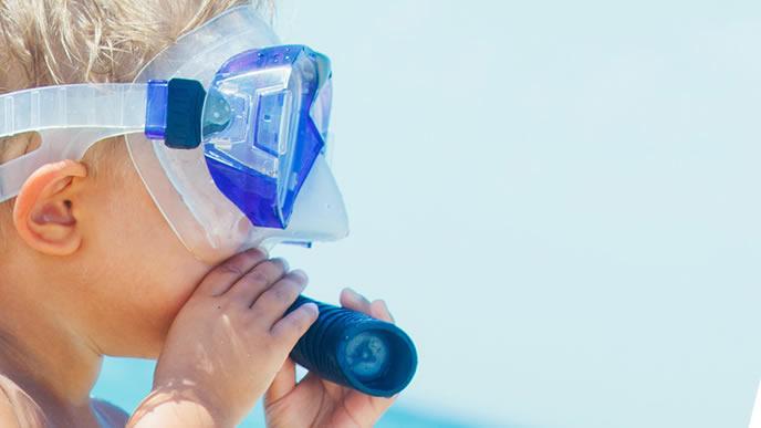 水中眼鏡とシュノーケルを装備して泳ぐ気マンマンの子供