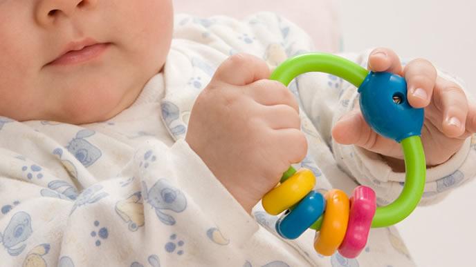 ラトルで遊ぶ新生児の赤ちゃん