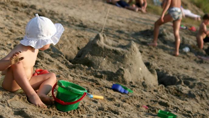 一人砂浜で遊ぶ赤ちゃん