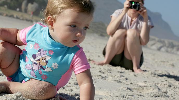 赤ちゃんの海デビューを写真に収めるママ