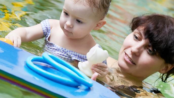 初めてのプールをママと一緒に遊ぶ赤ちゃん