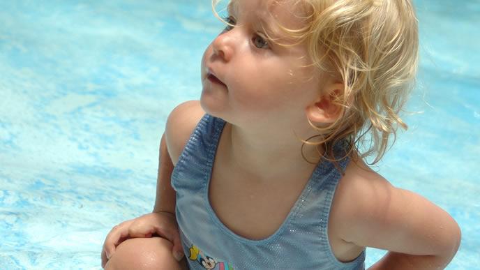 プールの浅瀬で一休みする赤ちゃん