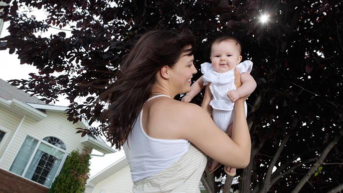 赤ちゃんを抱え日光浴をするママ