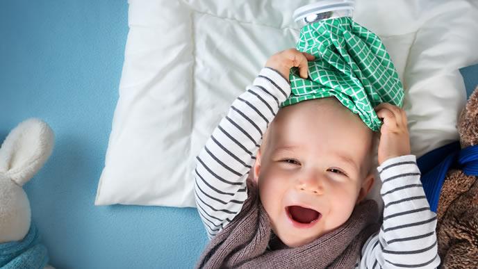 咳が止まり笑顔で氷枕で遊ぶ赤ちゃん