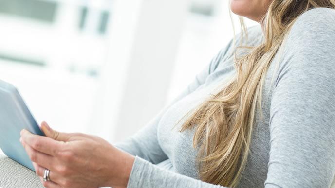 パソコンを使いインターネットで胎動の対処法を探す妊婦