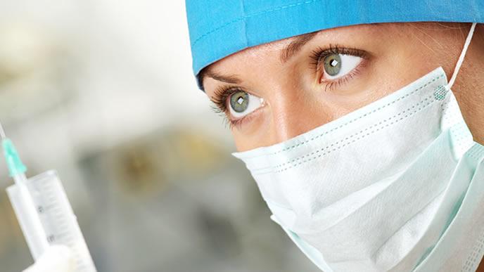 予防接種のワクチンを注射するために準備する医師