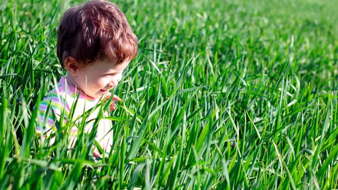 夏の昼間に外で一人遊びをする男の子