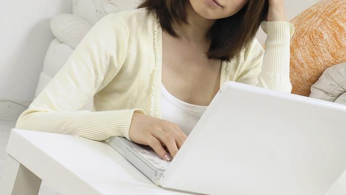 ノートパソコンで妊娠中の体の変化を調べる女性