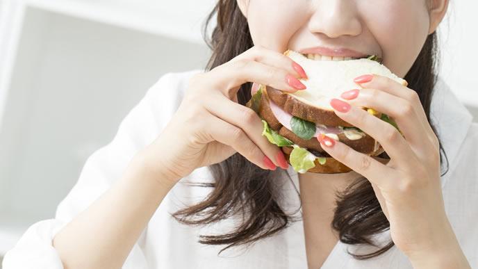 つわりが終わり大好きなサンドイッチを頬張る女性