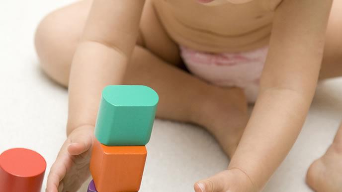 夏に裸で積み木遊びをする赤ちゃん