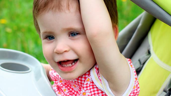 ベビーカーに乗りながら外ではしゃぐ赤ちゃん