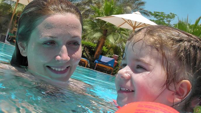 ママと一緒にプールで遊ぶ赤ちゃん