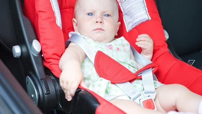 ベビーシートに乗せられ不服な赤ちゃん