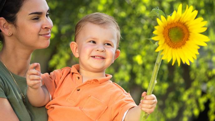 赤ちゃんと一緒に夏のヒマワリを見に来たママ