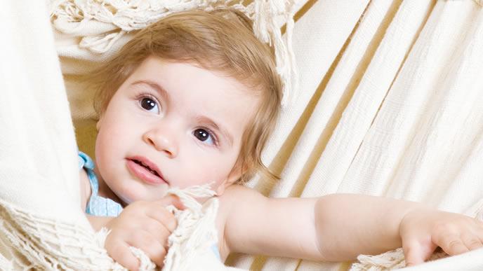夏に似合うベージュのシーツで遊ぶ赤ちゃん