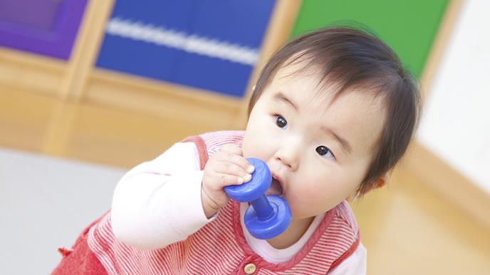 お腹がへっておもちゃを口にする赤ちゃん