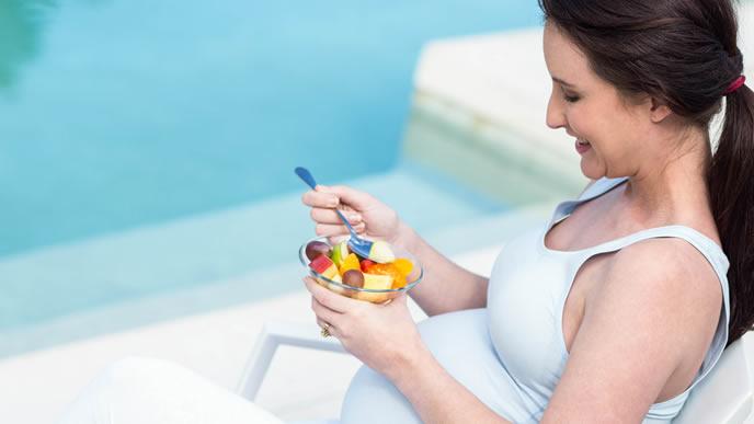 プールサイドでフルーツを食べる妊婦