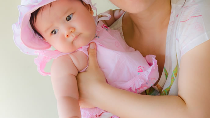 ママに抱っこされているピンクの服をきた赤ちゃん