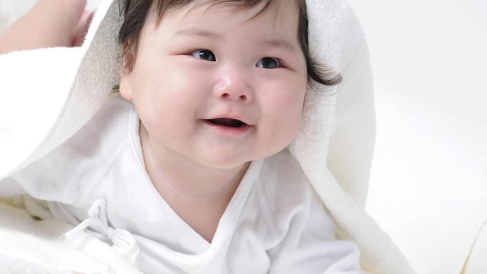 タオルをかぶって室内で遊ぶ赤ちゃん