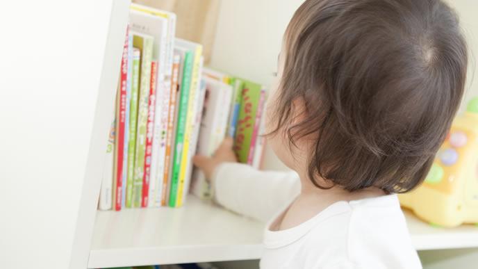 絵本に興味があり手にとる赤ちゃん
