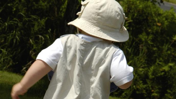 元気に駆け出す帽子をかぶった男の子